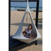 """Produktfoto - Das Cacoon Songo in der Farbe """"Mond"""" - aufgehangen an einem Holzkonstrukt am Strand - im Zelt ein Junge, daneben eine Frau - im Hintergrund sind Fischerboote und das Meer zu sehen"""